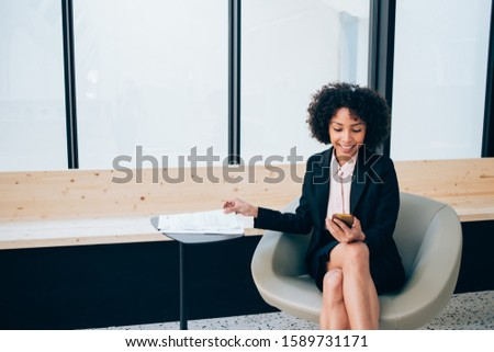 Smiling prosperous female entrepreneur reading information from website browsed on cellular indoors, positive black businesswoman in formal suit watching video online via mobile phone and 4G internet