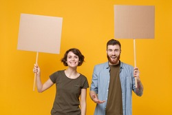 Smiling protesting young two people guy girl hold protest signs broadsheet blank placard on stick isolated on yellow background studio portrait. Protests strikes pickets concept. Youth against city