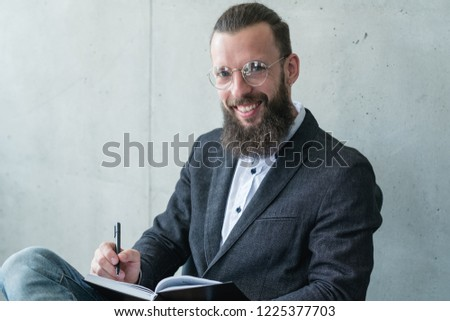 smiling psychologist counsellor or shrink writing in his diary during consultation