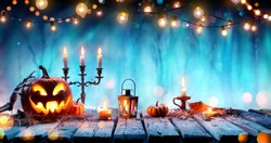 Smiling Pumpkin And Candelabrum On Table In Spooky Forest