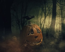 Smiling pumpkin in a web and black crow sitting on it with cemetery graves on background of scary dark sky in a bewitched, charmed, enchanted magic wood. Scary scenery, Happy Halloween poster concept