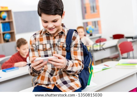 Smiling pupil in checkered shirt with backpack using smartphone in classroom #1350815030