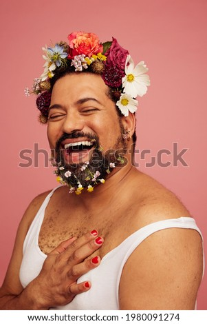 Smiling queer wearing makeup and tank top. Cheerful drag queen wearing flowers in his head and beard. Foto stock ©