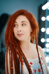 Smiling red-haired girl with long dreadlocks. Curious cute woman looks away. Hippie or boho style. Portrait of female with ginger dreads in beauty salon. Unusual coiffure.