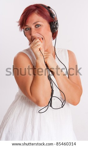 Smiling red headed woman wearing headphones - stock photo