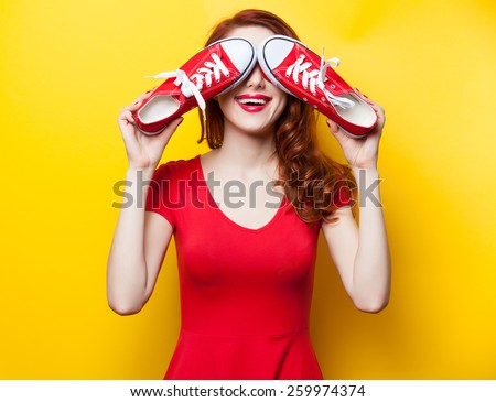 Smiling redhead girl with gumshoes on yellow background