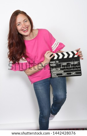 Smiling redhead woman in pink top with movie board isolated on white background