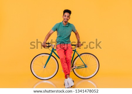 Smiling refined guy with black hair posing with pleasure near bike. Indoor portrait of enthusiastic african man with green bicycle.