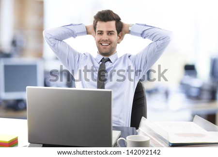 Smiling relaxed businessman leaning back in his chair in front of his desk and laptop in office. He wears shirt and tie.