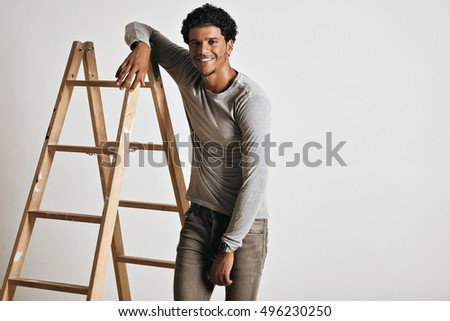Smiling relaxed tall muscular young model wearing a plain heather gray longsleeve t-shirt and slim gray jeans leaning on a wooden stepladder isolated on white. stock photo
