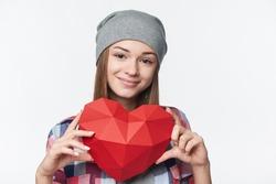 Smiling relaxed teen girl holding red polygonal paper heart shape, studio portrait