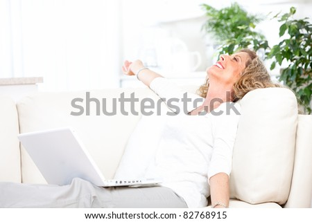 Smiling relaxing woman with laptop. Cosy home.