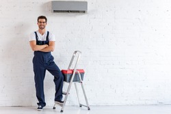 smiling repairman standing under air conditioner near stepladder and toolbox and looking at camera