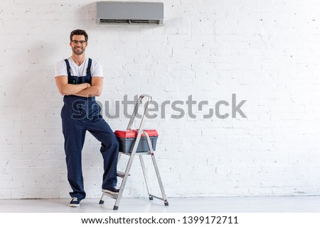 smiling repairman standing under air conditioner near stepladder and toolbox and looking at camera #1399172711