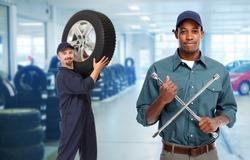 Smiling repairman with tire wrench in car repair service.