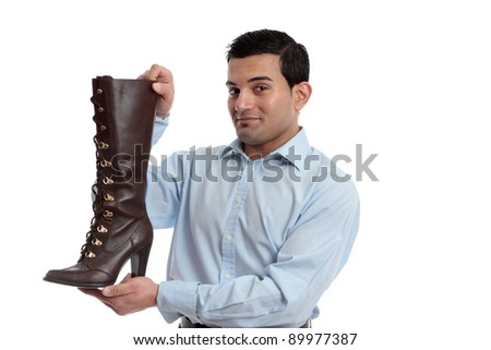 Smiling retail salesman holding or showing off a ladies leather boot.