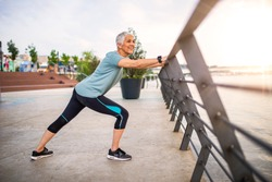 Smiling retired woman stretching legs outdoors. Senior woman enjoying daily routine warming up before running at morning. Sporty lady doing leg stretches before workout
