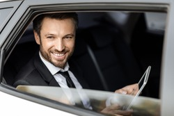 Smiling rich businessman in suit sitting in car, looking through window, using digital tablet, copy space. Wealthy handsome middle-aged man working on digital pad while going to business trip