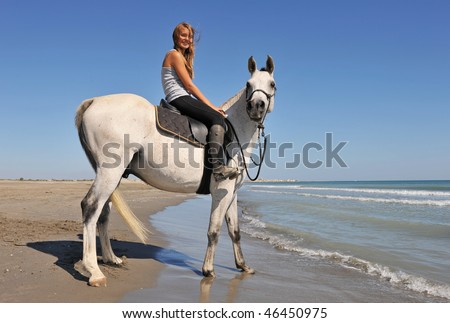 smiling riding teenager and her white horse on the beach - stock photo