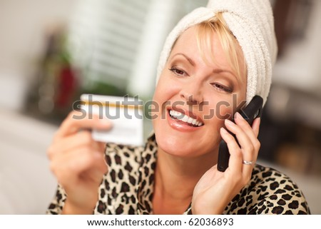 Smiling Robed Woman on Cell Phone Looking At Her Credit Card. - stock photo