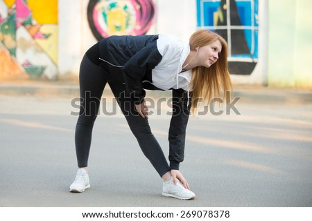 Smiling runner girl with earphones in sportswear doing stretching exercises before morning jogging on the sunny street in front of wall with bright colored graffiti, preparing for running