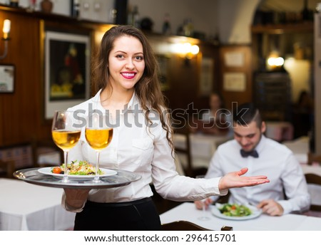 Smiling russian female waiter serving guests table in restaurant
