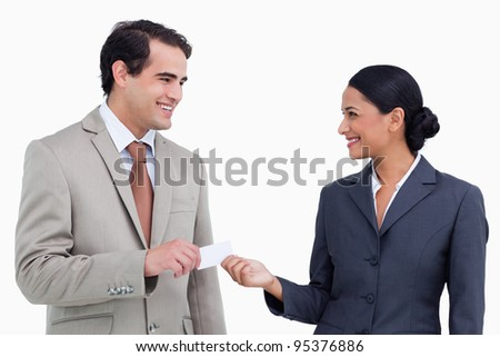 Smiling sales partner exchanging business cards against a white background