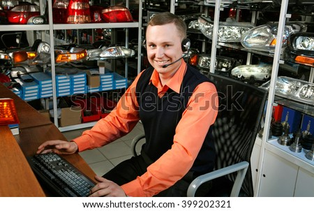 Smiling Salesman Auto Parts Store with a Computer #399202321