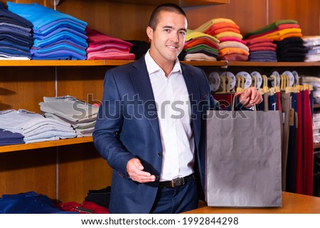 Smiling salesman holding out paper bag with purchases in modern clothing store