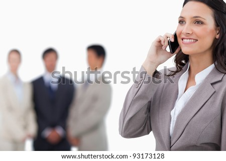 Smiling saleswoman on her mobile phone with team behind her against a white background - stock photo