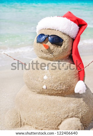 Smiling sandy snowman in red santa hat on the sea beach. Holiday concept can be used for New Year and Christmas Cards