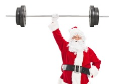 Smiling Santa holding a heavy barbell in one hand and looking at camera isolated on white background