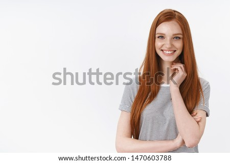 Smiling sassy good-looking ginger european young 20s girl student amused entertained touch neck looking intrigued gazing camera cannot wait summer holidays travel look hopeful, white background