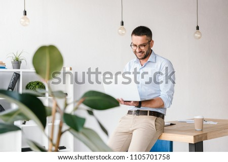 Smiling satisfied man 30s wearing white shirt sitting on table in office and having business chat on silver laptop