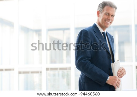 Smiling satisfied senior businessman looking at camera at office