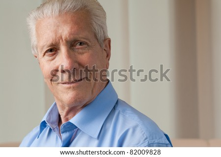 Smiling satisfied senior man looking at camera at home, copy space