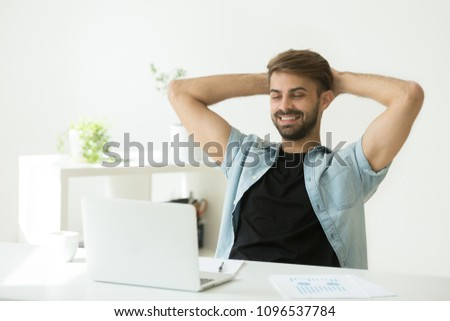 Smiling satisfied worker resting in chair during work break looking at laptop, happy with successful sales result, motivated with good news, happy with productive job. Rewarding concept, stay positive #1096537784
