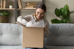 Smiling satisfied young woman customer sit on sofa unpack package open parcel, happy girl consumer holding cardboard box receive good online shop purchase at home, post mail shipping delivery concept