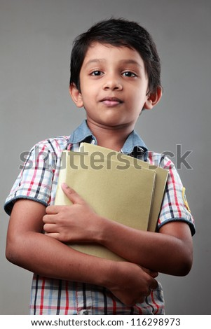 Smiling school boy with note books in his hands