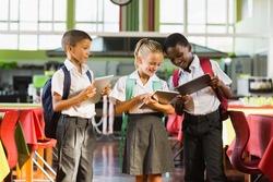 Smiling school kids using digital tablet in school cafeteria