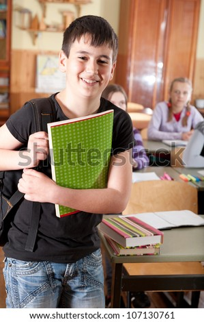 Smiling schoolboy with notebook in front of class