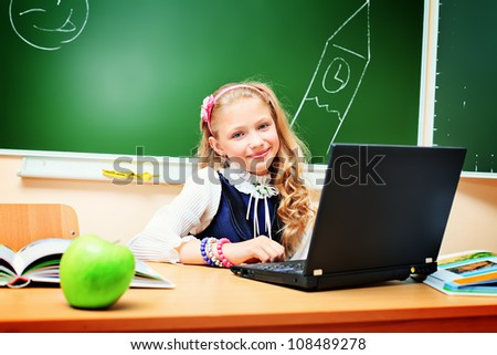 Smiling schoolgirl studying with her laptop at classroom.