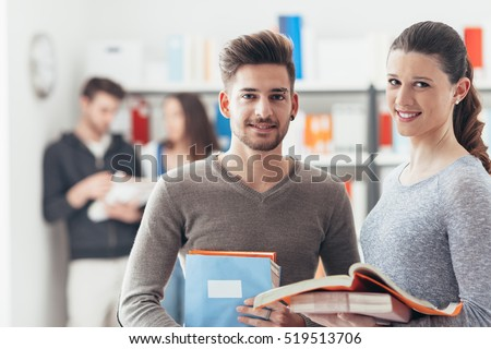 Smiling schoolmates holding books and studying together in the school library, learning and education concept