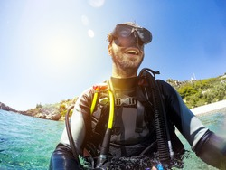 Smiling scuba diver portrait at the sea shore. Diving goggles on.