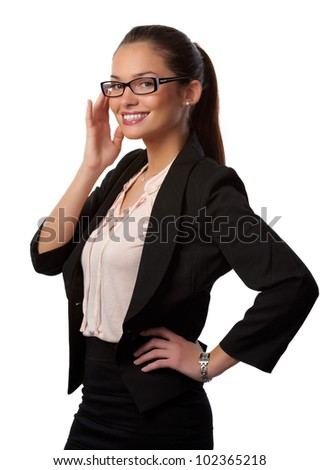 Smiling secretary brunette with glasses facing left 3/4 on white background. She is setting her glasses straight with her fingertips.