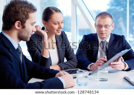 Smiling secretary looking at document held by her boss while listening to his explanation - Shutterstock ID 128748134