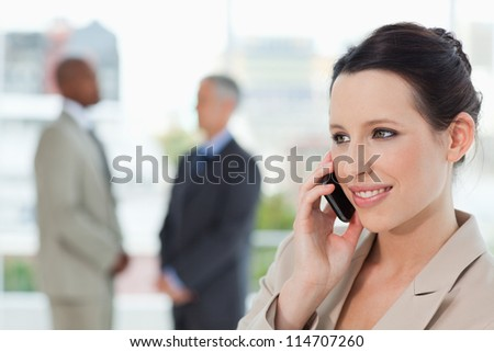 Smiling secretary talking on the phone while looking towards the side