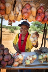 smiling self employed african woman at her street stall selling fresh  vegetables