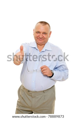 Smiling senior business man showing thumb up sign and holding glasses over cutout background - stock photo