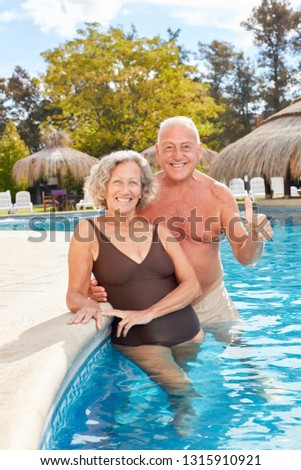 Smiling senior couple is standing with thumbs up in the pool of wellness hotel